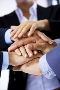 business people putting their hands on top of each other