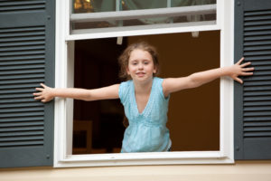 Little girl looking from the open window of country house